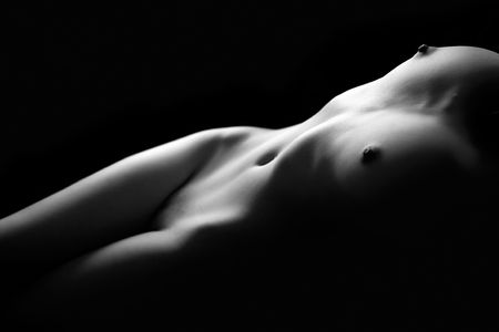 Monochrome art nude on black studio background