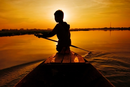 tour boats: Silhouette of boy paddling boat at sunset