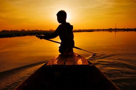 the boat on the river: Silueta de chico remando barco al atardecer