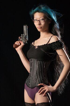 Dangerous Chinese woman with handgun on black studio background photo