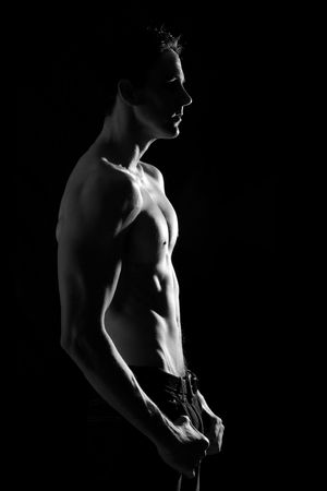 fits in: Lean and fit man on black studio background