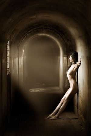 Artistic nude of beautiful woman in tunnel