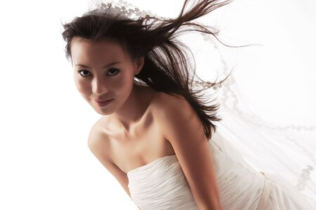 dress blowing in the wind: Beautiful Chinese bride on white studio background