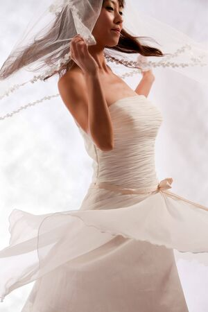 spins: Beautiful Chinese bride dances on white studio background