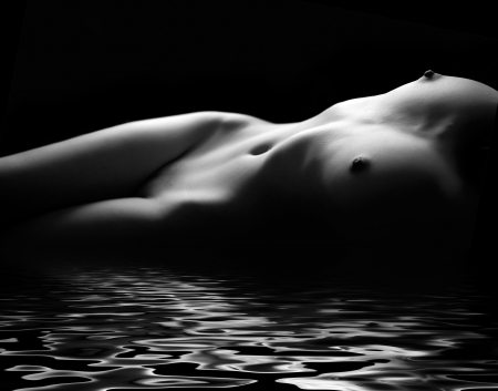 Monochrome art nude on black studio background