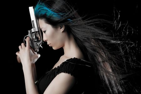 Mujer China peligrosa con pistola sobre fondo negro de estudio