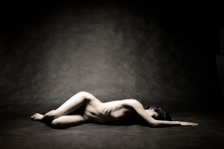 Nude woman laying on black studio background