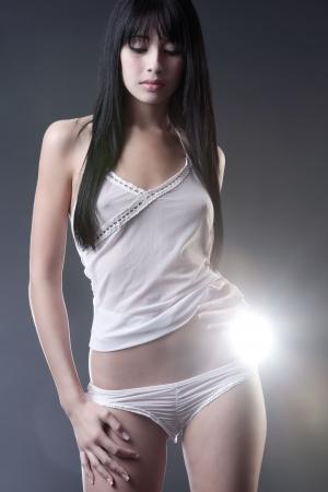 femme noire nue: Belle brunette en lingerie blanc sur fond de studio