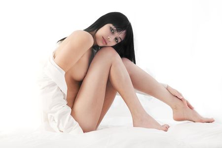 Beautiful Eurasian woman naked on bed, white background