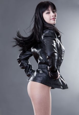 Beautiful fashion model in leater jacket on studio background photo