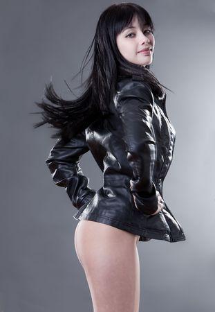 eurasian: Beautiful fashion model in leater jacket on studio background Stock Photo