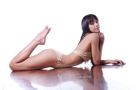 lying on floor: Beautiful Eurasian girl in swimsuit on white studio background