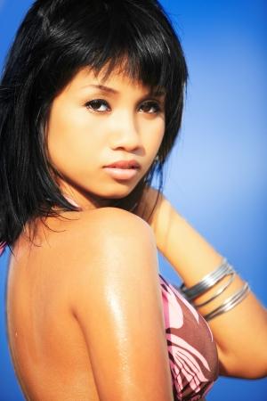 Beautiful Asian model wearing bikini on blue sky background