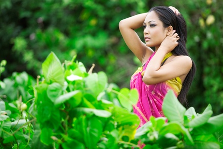 Beautiful Asian model outdoors in lush green garden