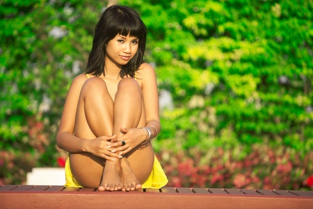 Beautiful Asian girl sits in garden, lush green background Stock Photo