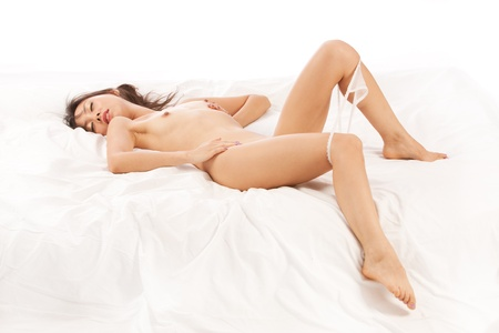 Beautiful Chinese girl lays naked in bed, white background Stock Photo