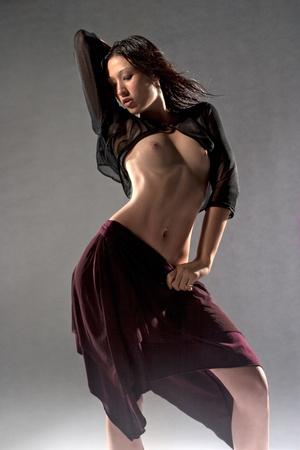 Topless fashion model on grey studio background Stock Photo