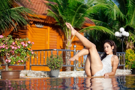 Sexy Asian woman frolics on edge of pool in tropical resort in Thailand