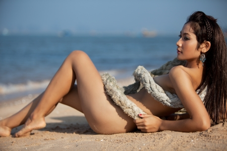 Beautiful Thai woman laying naked on the beach wrapped up in rope.