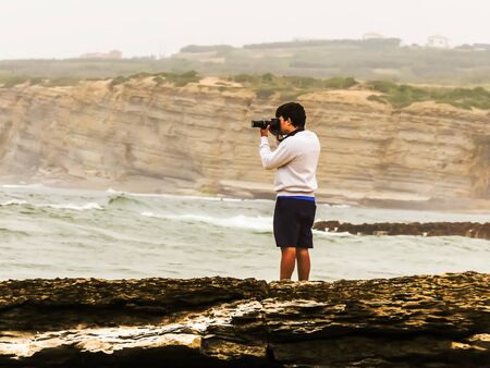Man photographing the sea on a rocky dike