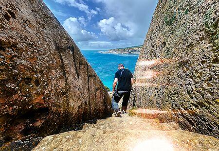 Man descending on a stone ladder