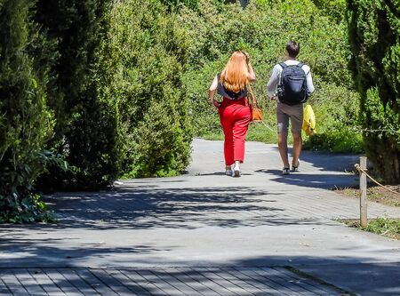 A couple walking down an alley in a city park
