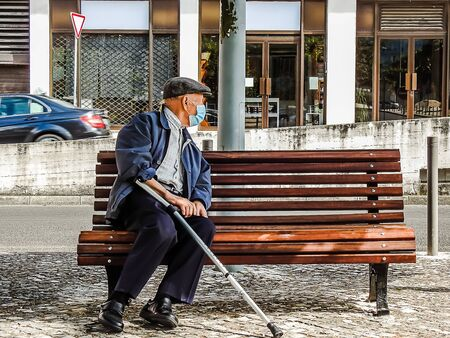 An old man sitting on a bench during a pandemic with a mask on Banque d'images
