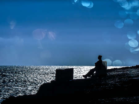 The silhouette of a woman sitting on a bench by the ocean in the sunset light Banque d'images