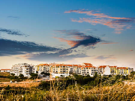 View with a residential neighborhood near the sunset with a sky with fine and colorful clouds
