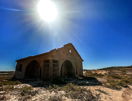 A ruined house on a field with the sun above shining in the blue sky