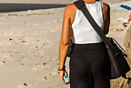 Woman's torso with white T-shirt and black skirt on the sand on the beach