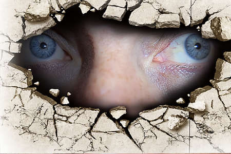 The blue eyes of a man looking through a crack in the wall