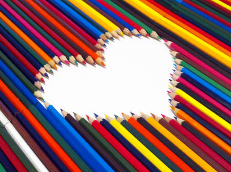 colored pencils, laid out in the shape of a heart on a white background photo