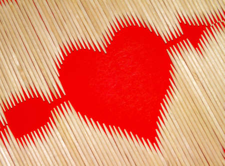 heart pierced by an arrow, laid out with toothpicks on a red background photo