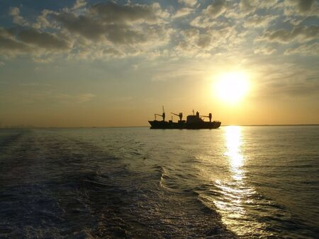 siluet: Siluet of ship on a background sunset in a bay                                Stock Photo