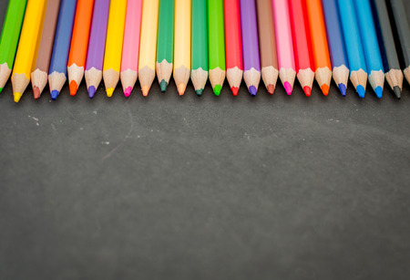 coloured background: Colorful pencil crayons on a blackboard background