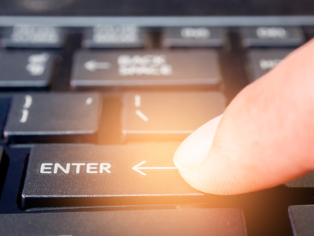 forefinger: forefinger pressing ENTER button on your keyboard. Start work concept.