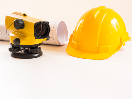 theodolite and construction helmet, rolls and plans. on white background. Construction industry concept.