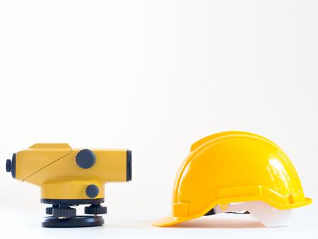 theodolite: theodolite and construction helmet on white background.