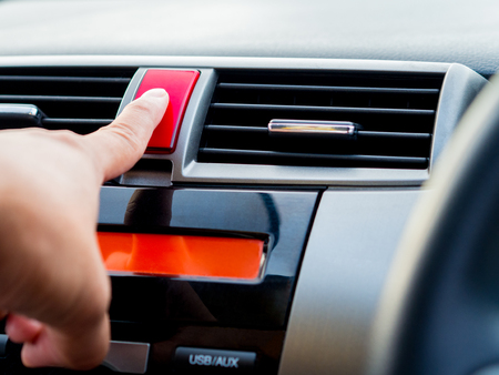 flashers: Close up, man hand push emergency light button in car.