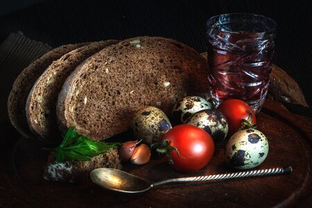 Fresh bread on wooden table,vintage filter, Traditional black rye-bread on dark background,  Red cherry tomatoes with sliced bread and quail eggs and glass of red wine, vintage still life
