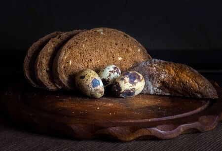 Fresh bread on wooden table,vintage filter, Traditional black rye-bread on dark background,   sliced bread and quail eggs, vintage still life Stock Photo