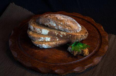 Fresh bread on wooden table,vintage filter, Traditional black rye-bread on dark background,   sliced bread, vintage still life