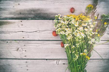 trompo de madera: ramo del verano de margaritas y Hypericum, con bayas de fresas en el fondo de madera rústica, con copia espacio, flores silvestres, hierbas medicinales en una mesa de edad, vista desde arriba Foto de archivo