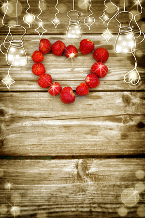 greeting christmas: Old grunge wooden board with light bulb border, strawberry in the shape of a heart.  Selective focus and place for text. Toned. Can be used as greeting card, wedding invitation, Christmas, holiday.