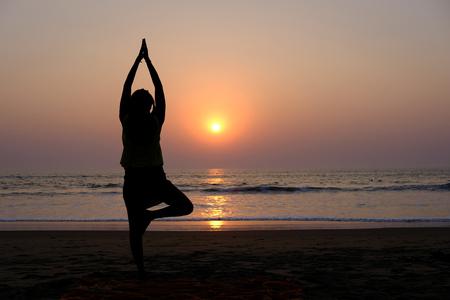 Womans silhouette doing yoga (tree pose) on the beach at sunset, Gokarna (Karnataka, India)