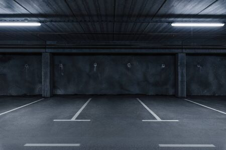 Sci-fi looking dark and moody underground parking lot with fluorescent lights on.