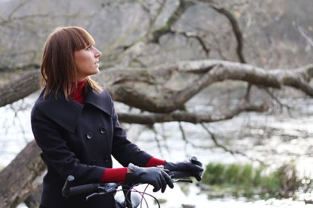 Young female bicycle rider in autumn park photo