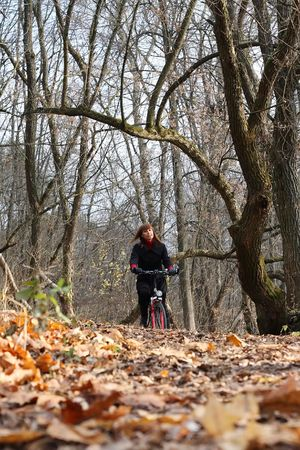 Young female bicycle rider in autumn park Stock Photo - 6959927