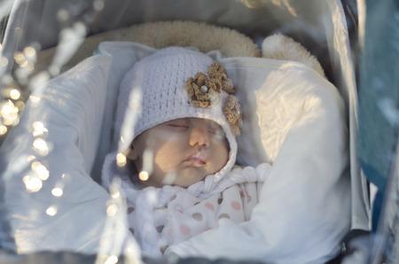 perambulator: A cute little baby is sleeping under the raincoat in the perambulator Stock Photo